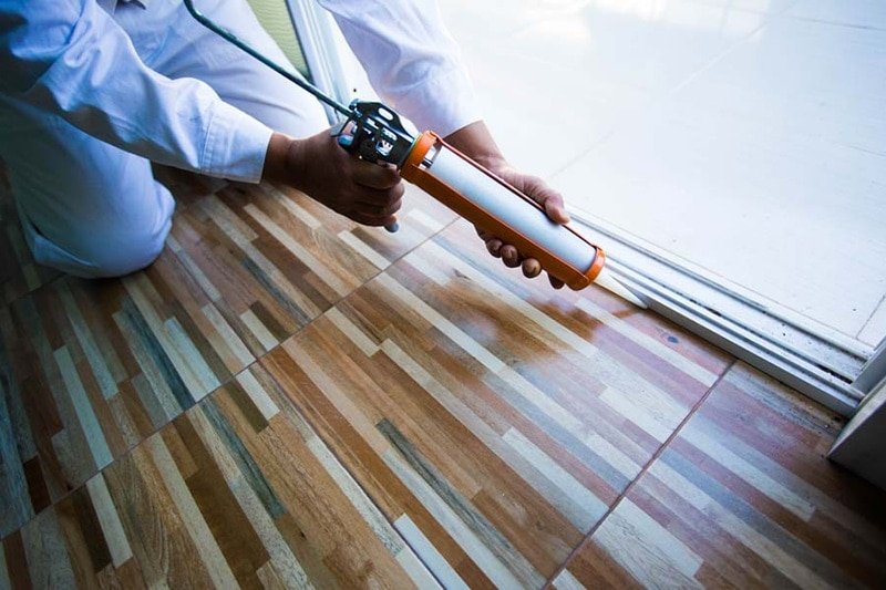 Construction workers install doors - windows and use silicon and sealant