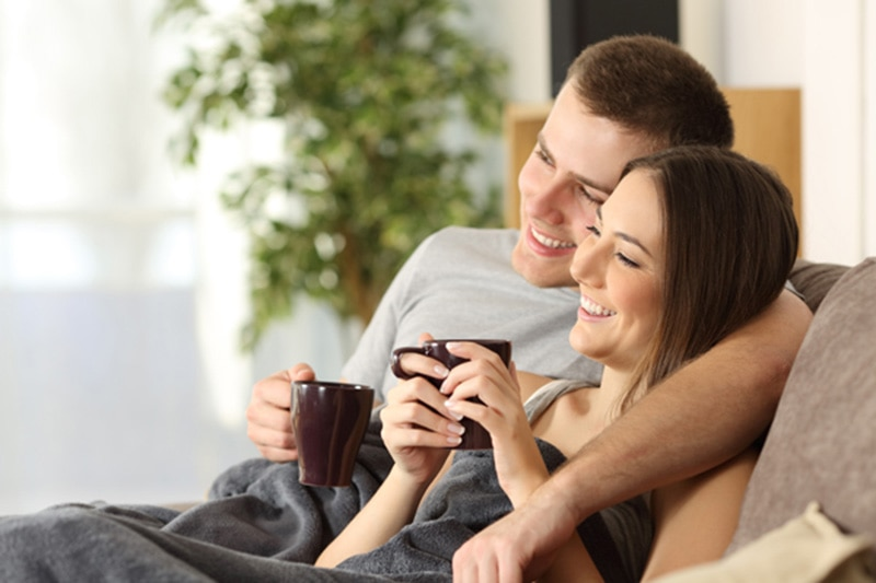 how can I make my furnace last longer?, happy couple sitting on the couch together with mugs