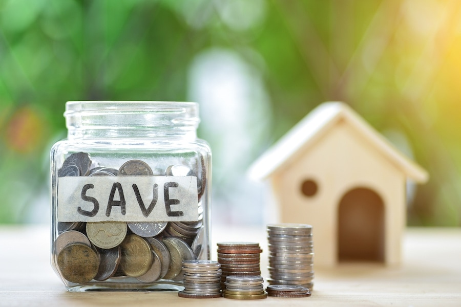 Home and money jar representing the many HVAC ways to go green in your home this summer.