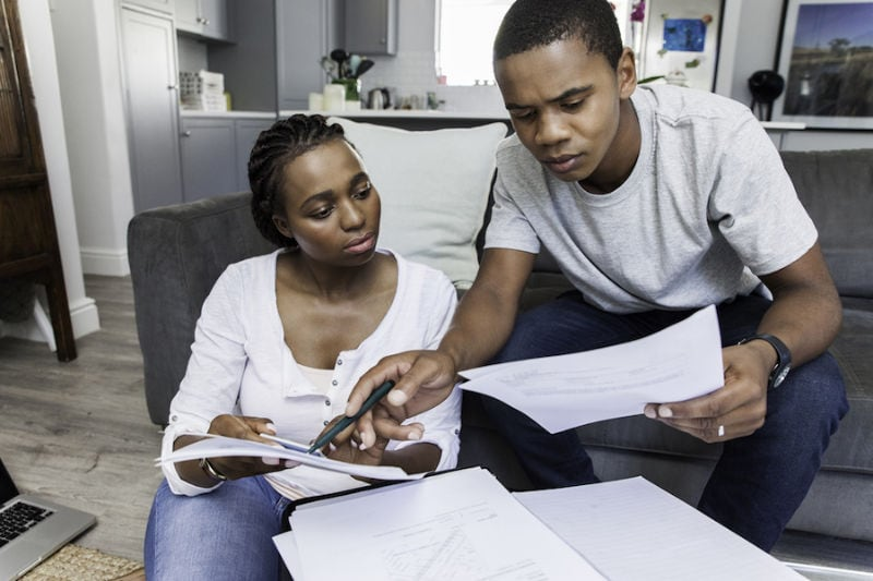 Couple Looking Over Bills trying to determine how to afford a new AC system and other HVAC equipment for their home.