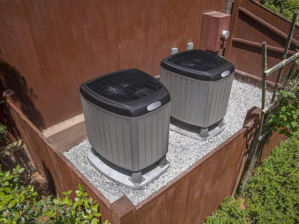 Residential heating and air conditioner compressor units near residential house
