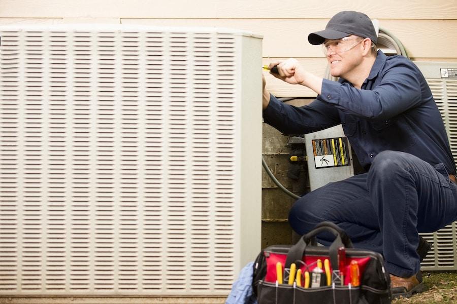 Technician inspecting AC unit and following maintenance checklist.