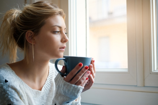 Should I Get an 80% or 95% Furnace?, girl drinking out of mug looking out her window